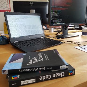 Ein Schreibtisch meinem Laptop samt externen Bildschirm im Hintergrund. Im Vordergrund zwei Clean Code-relevante Bücher